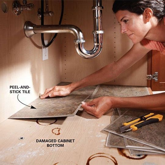 Use peel-and-stick tiles to cover up a leaked-on cabinet bottom.