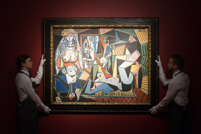 """Christie's employees pose for pictures with a painting by Pablo Picasso called """"Les femmes d'Alger (Version """"O"""")"""" at the auction house in London."""
