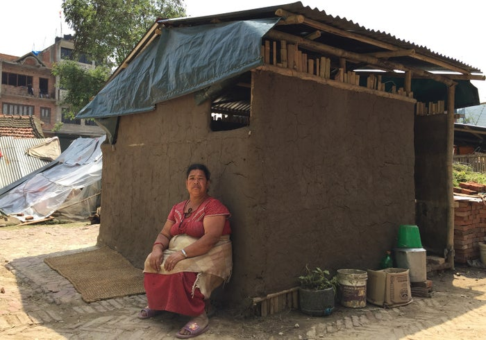 Januki Mali, 45, sits in front of a shelter built by a group of Kathmandu University students after she lost her home during the earthquake.