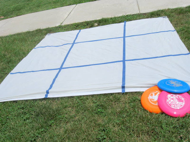 DIY this backyard tic-tac-toe game with a shower curtain, tape, and Frisbees.