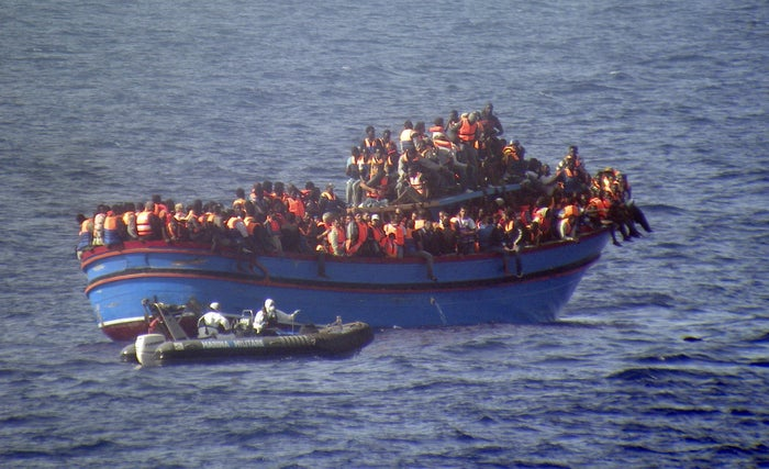 An Italian boat approaches a boat overcrowded with migrants and asylum-seekers in the Mediterranean, June 2014.