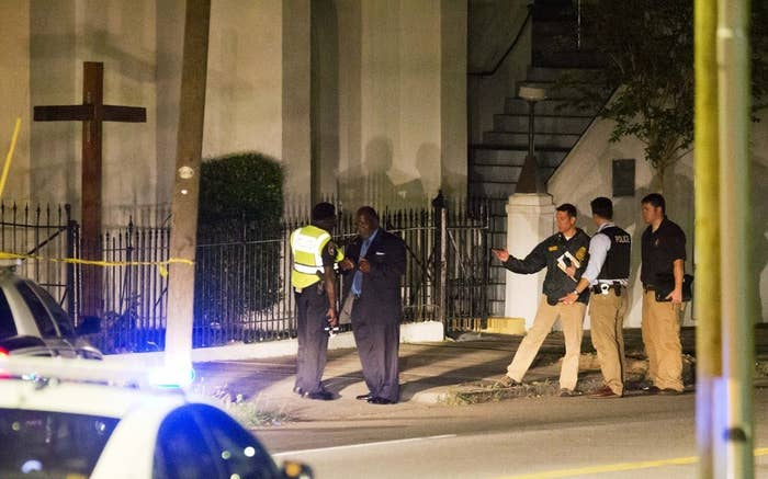 Police stand outside the Emanuel AME Church following a shooting Wednesday.