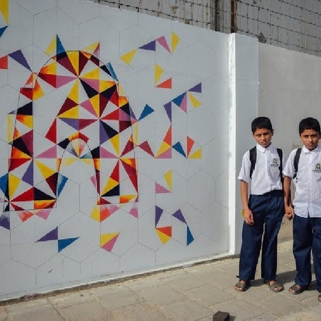 Children stand beside a geometric drawing of Mazar-e-Quaid, the tomb of Muhammad Ali Jinnah, the founder of Pakistan.