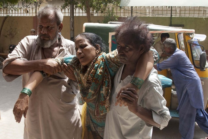 Family members rush a woman to a hospital suffering from heatstroke in the city of Karachi on Tuesday.