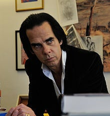 """Nick Cave is best known for being the frontman of the Australian alternative rock band Nick Cave and the Bad Seeds. He is often referred to as rock music's """"Prince of Darkness"""" because of his emotionally charged lyrics that often refer to death, love, religion and violence. His songs have appeared in movies such as Batman Forever, Scream, The X-Files, and Harry Potter and the Deathly Hallows – Part 1. Cave worked as the composer for the films The Proposition, The Assassination of Jesse James by Coward Robert Ford, and The Road. Cave also wrote the screenplay for The Proposition and Lawless."""