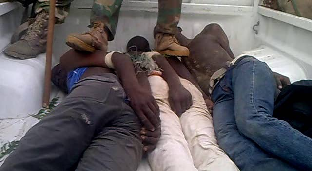 Three men identified as Boko Haram suspects during a 'screening' operation by the Nigerian military in Bama, Borno state, Nigeria, in 2013. The image is a still taken from a video of the arrests.