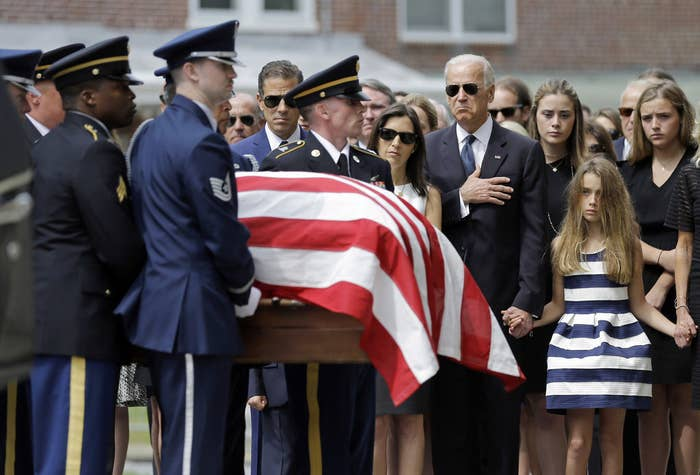 Vice President Joe Biden, accompanied by his family, holds his hand over his heart as he watches an honor guard carry a casket containing the remains of his son. Standing alongside the vice president are Beau's widow Hallie Biden, left, and daughter, Natalie.