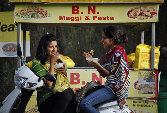 Indian girls eat noodles at a roadside stall in western India on June 4.