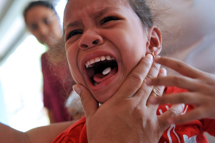 A girl cries while receiving a deworming pill in Managua, Nicaragua.