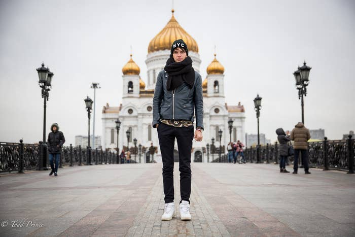Kolya, a engineer, crosses a pedestrian bridge behind Christ the Savior cathedral on a chilly Moscow autumn day sporting an NYC hat.