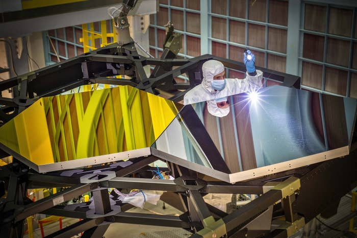 Two test mirror segments for the James Webb Space Telescope are inspected by an optical engineer. There will be 18 mirror segments in total, all covered in a thin layer of gold, as seen on the segment on the left of this photograph.