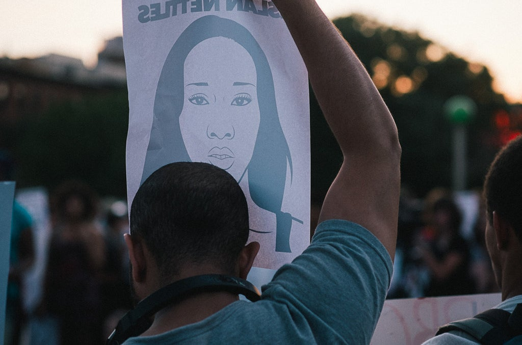 A man holds a poster of Islan Nettles.
