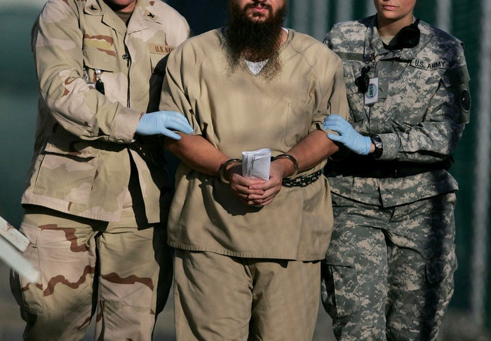 A shackled detainee escorted by two U.S. military personnel at the detention facility on Guantánamo Bay U.S. Naval Base in Cuba in 2006.