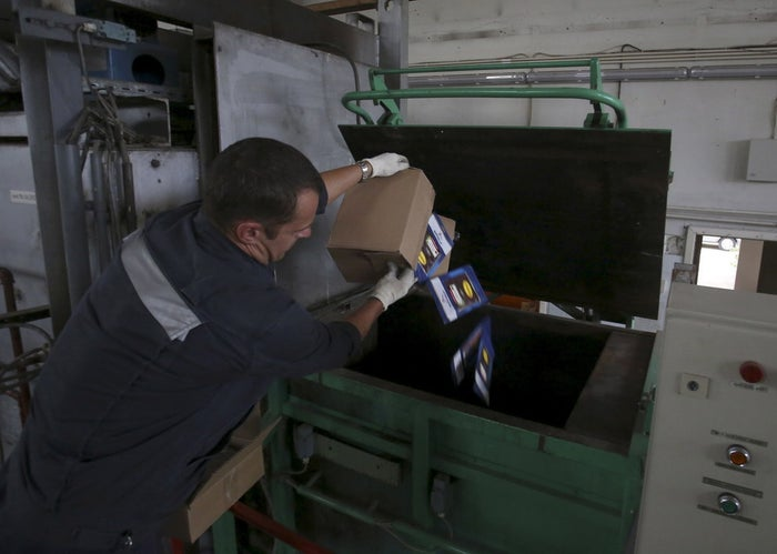 An employee throws sliced and packed meat into a furnace during the destruction of illegally imported food falling under restrictions at a customs house at Pulkovo airport in St. Petersburg, Russia on August 6, 2015.