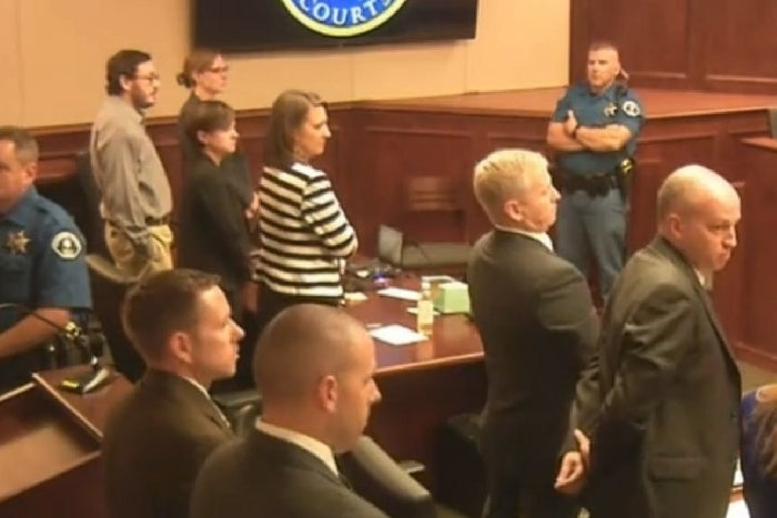James Holmes, top left in tan shirt, listens to the verdict forms being read.