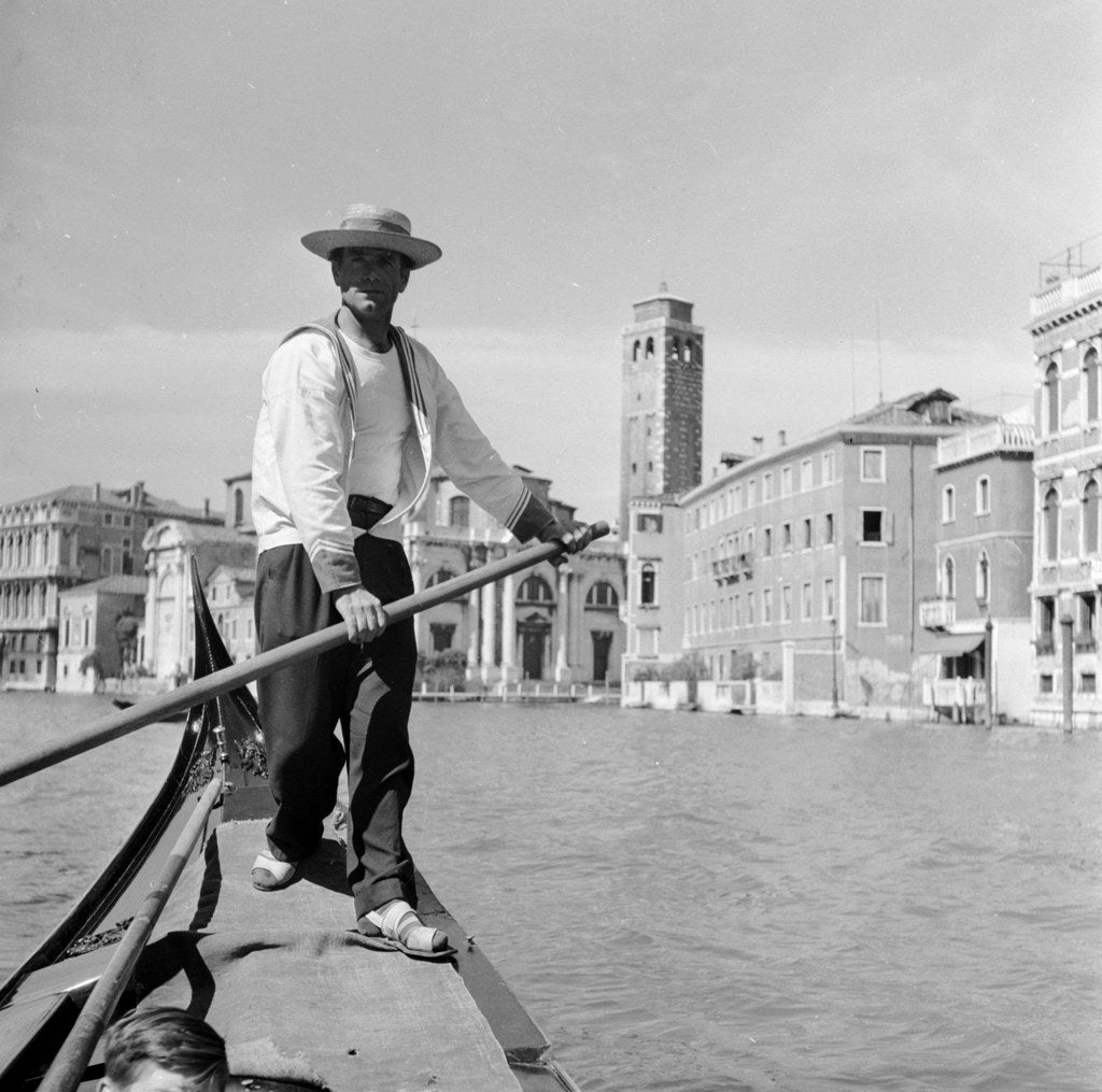 A gondolier navigates his way through Venice. Circa 1950.