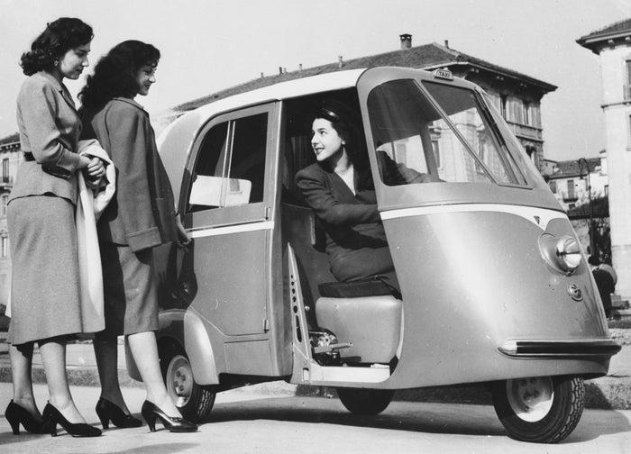 Deux femmes hèlent un taxi-scooter Vespa à Milan. Avril 1952.