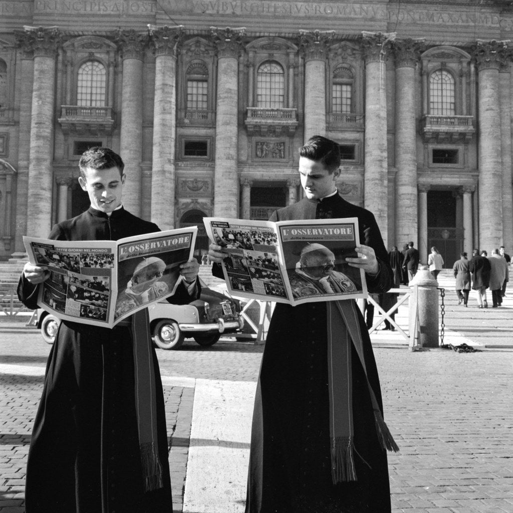 A pair of priests read 'L'Osservatore' outside St Peter's Basilica in Vatican City. Circa 1955.