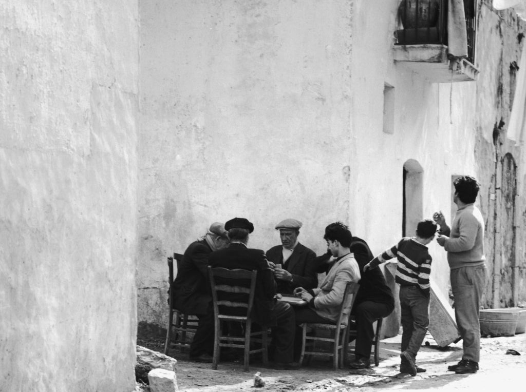 A group of unemployed men playing cards on a street corner, Sicily. Circa 1955.