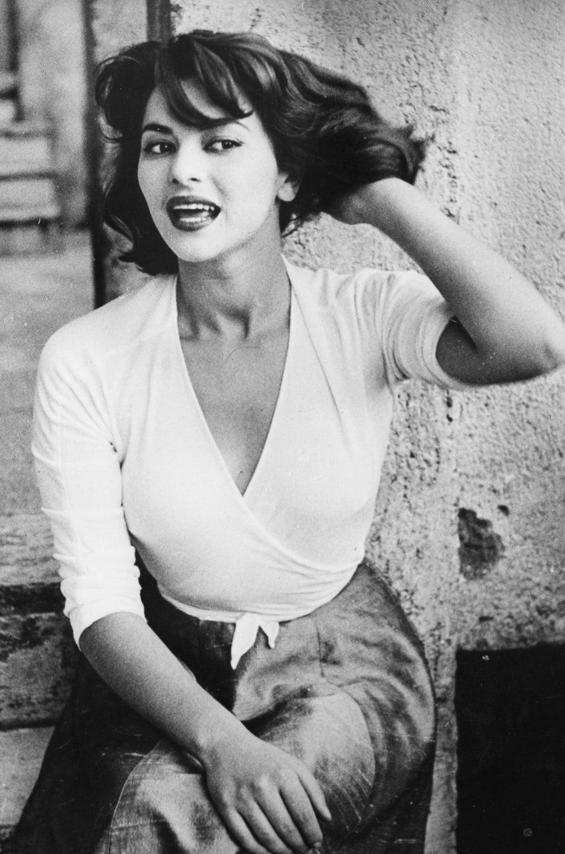 Portrait de l'actrice italienne Giovanna Ralli assise sur une marche en pierre. Mai 1955.
