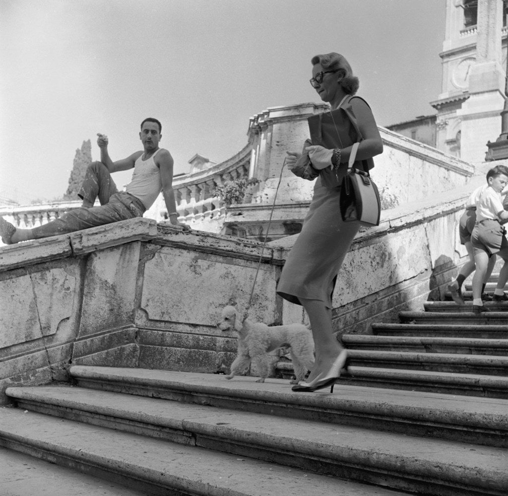 An Italian man watches an American tourist walking her poodle down the Spanish Steps in Rome. Circa 1955.