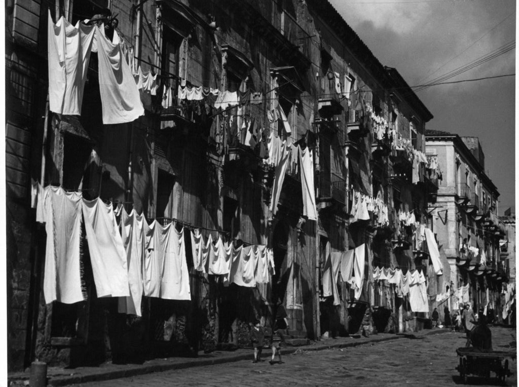 Laundry is pinned across an entire building on wash day in Sicily. 1955.