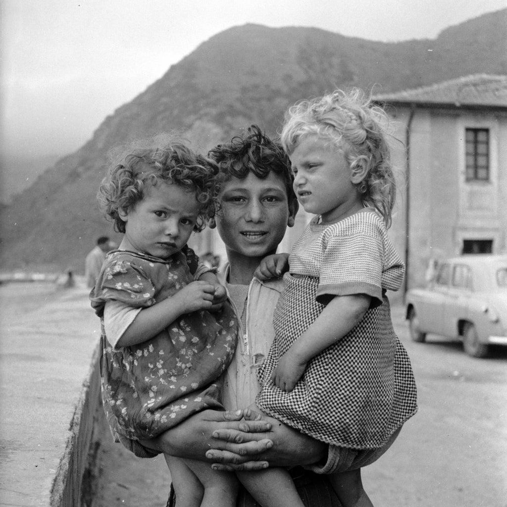 Le fils d'un pêcheur s'occupe de ses deux sœurs pendant que ses parents travaillent en mer au large de la Calabre. Vers 1950.
