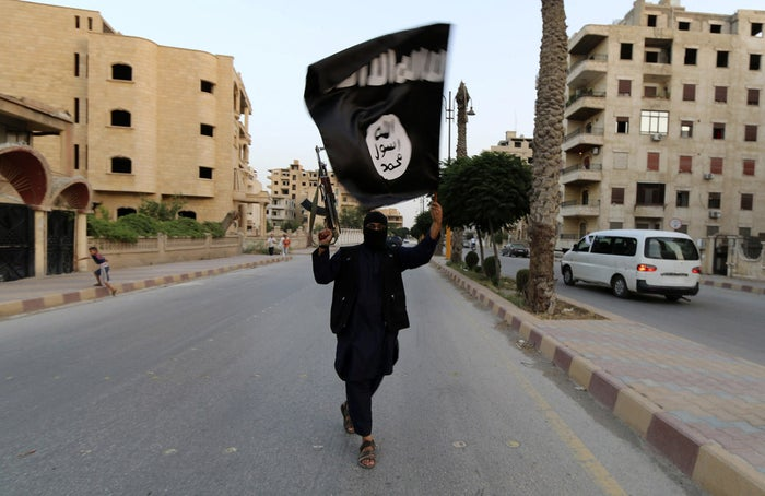 A militant waves an ISIS flag in Raqqa, Syria, in June 2014.