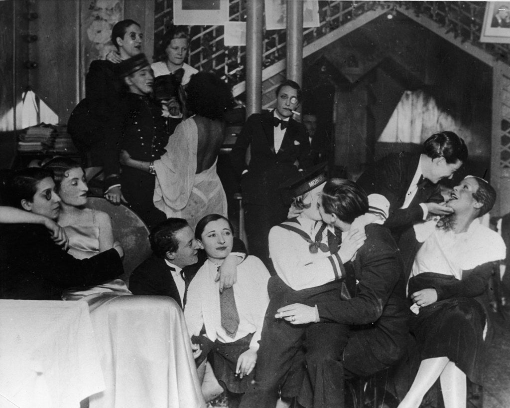 A group of patrons, many dressed as men in tuxedos, and some with monocles, sit, talk, laugh, and kiss, at 'Le Monocle' a famous night club for women in Paris. 1920s.