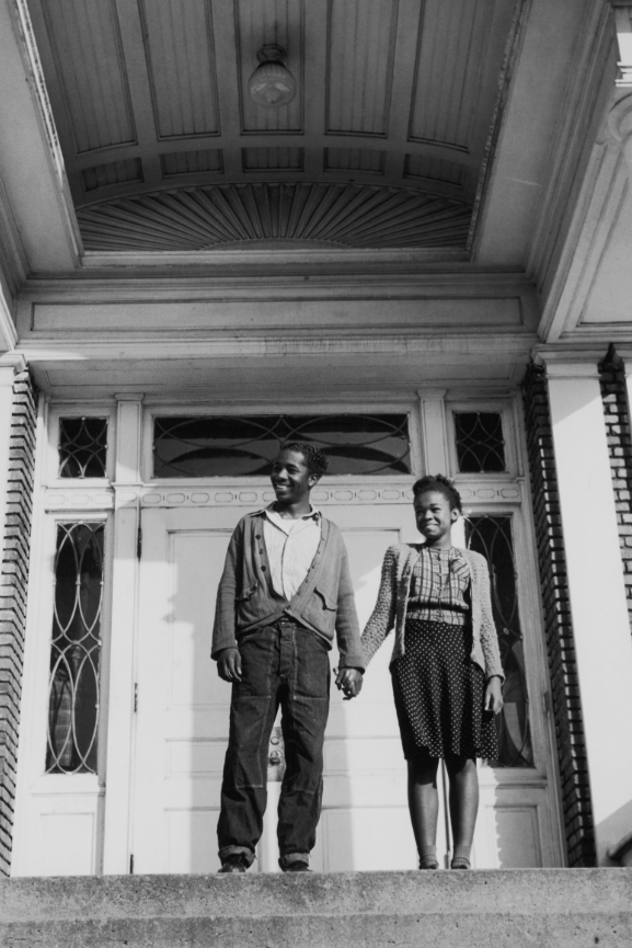 A teenage couple holding hands on the porch of a large house, USA. Circa 1955.