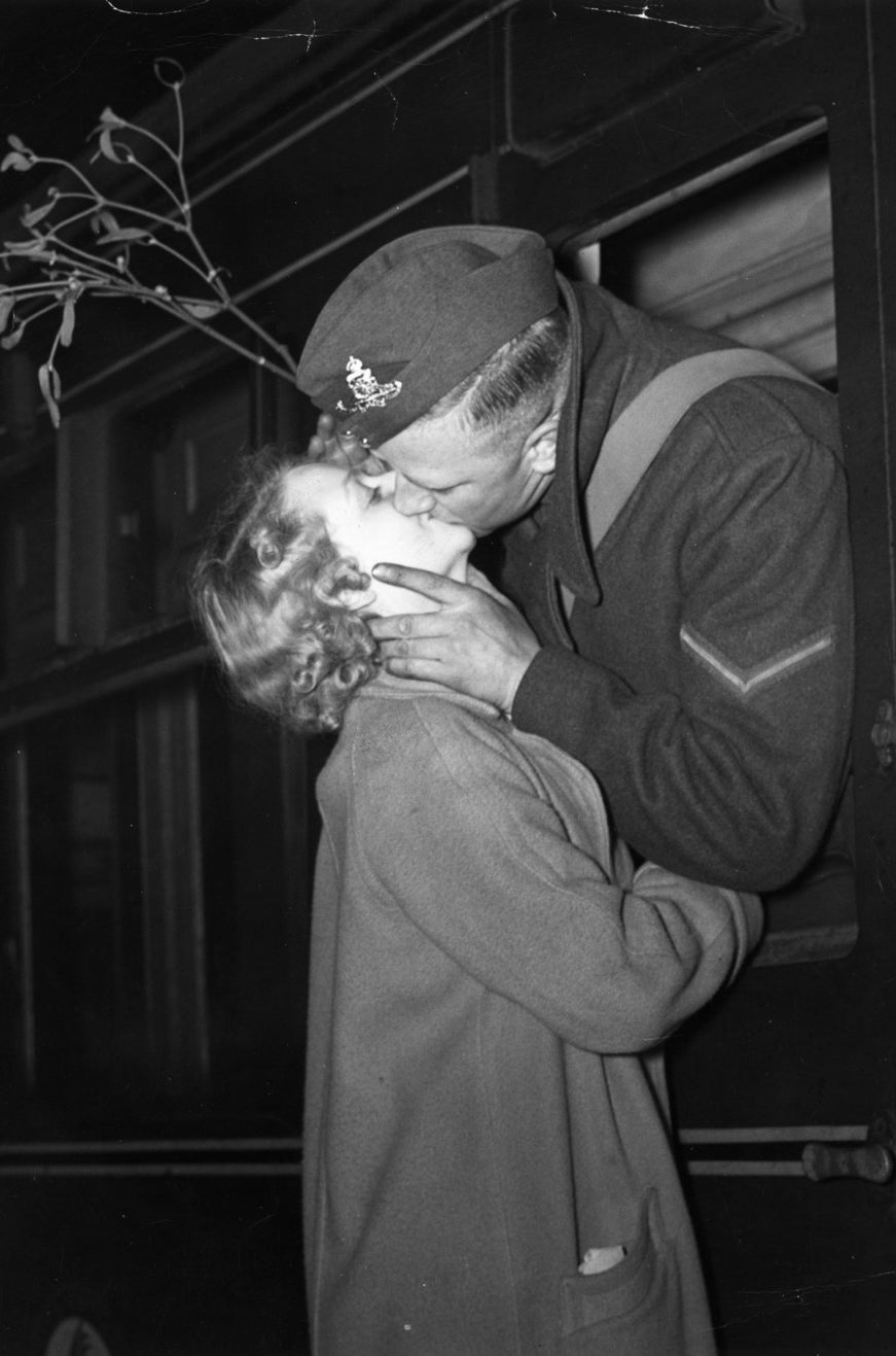 A soldier leaving a London railway station to re-join his unit took along a sprig of mistletoe to make sure he got his Christmas kiss. December 1939