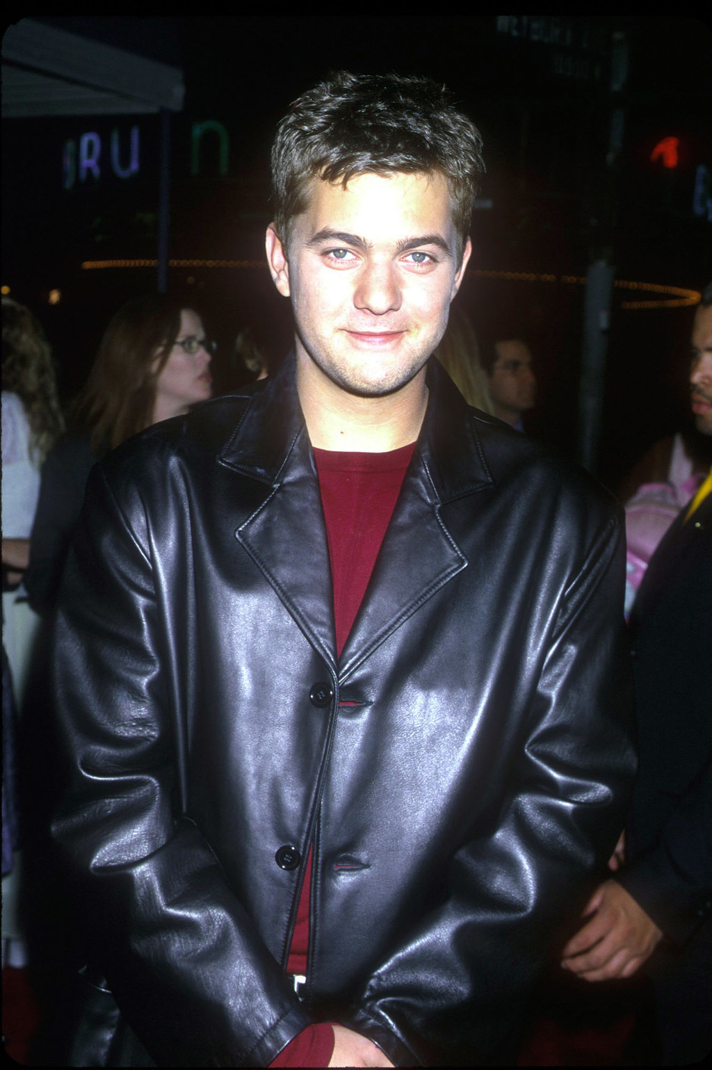 in a large pleather jacket