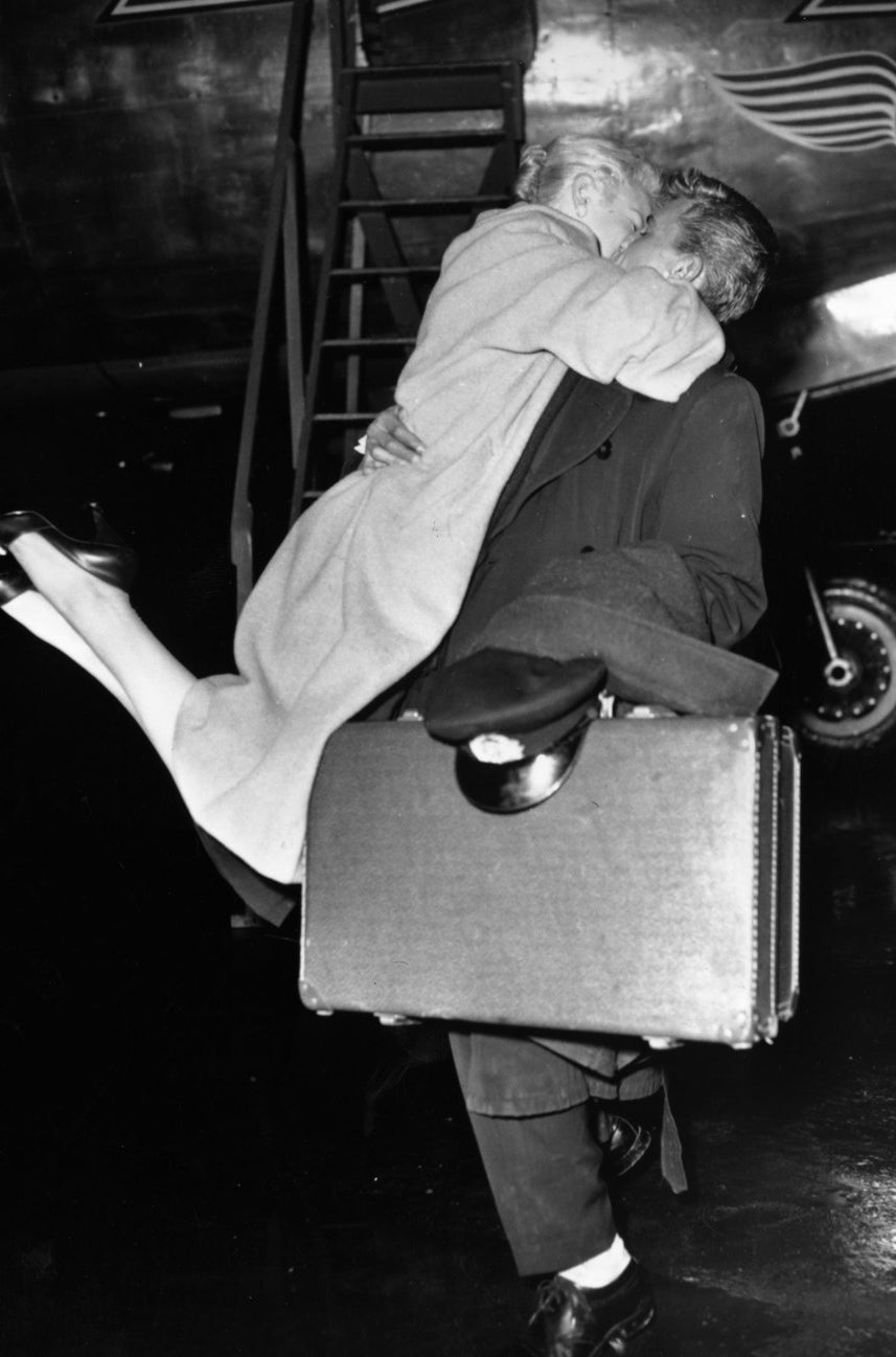 A woman greeting her Skymaster Aircrew husband with enthusiasm after his flight to Albania.