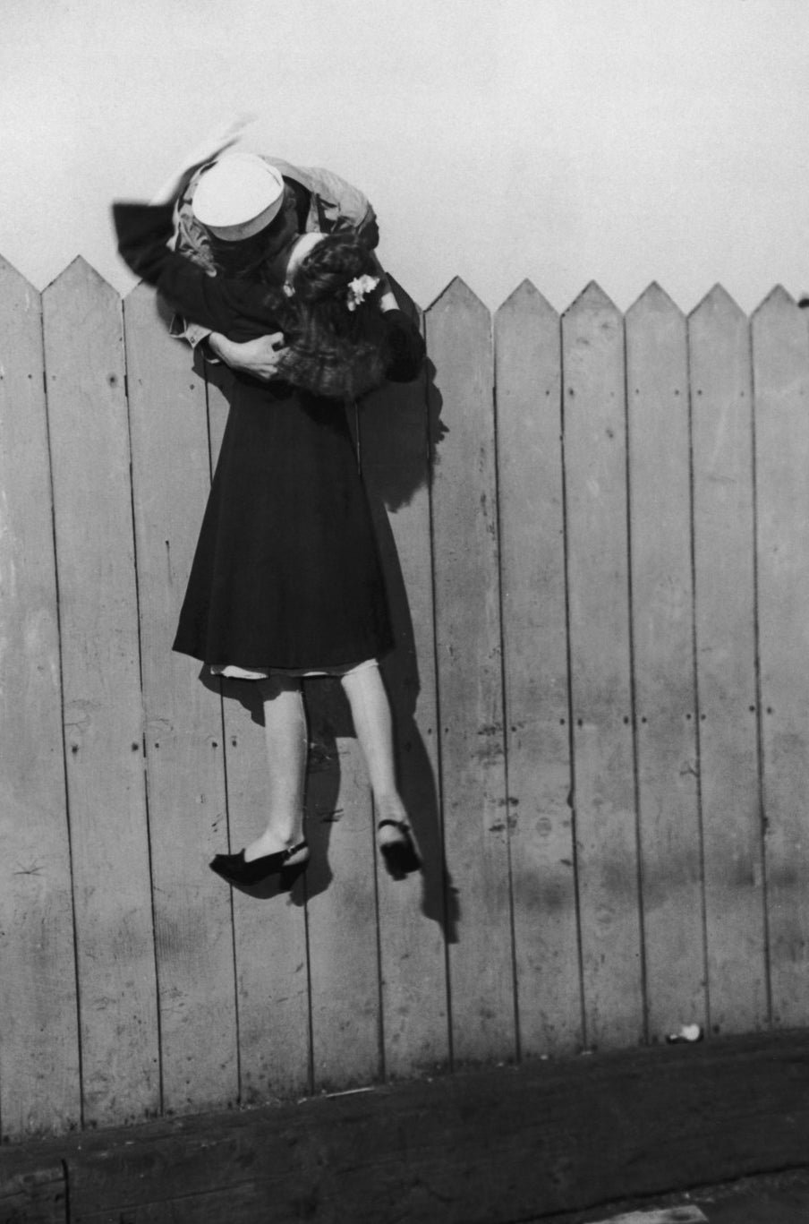 A sailor leans over a picket fence and lifts his girlfriend up for a kiss. 1945.