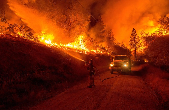 A firefighter douses flames from a backfire while battling the Butte Fire near San Andreas, California.