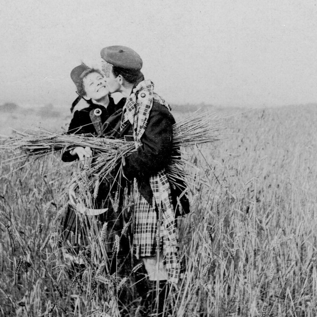A man in a kilt kisses a girl in a rye field. Circa 1910.