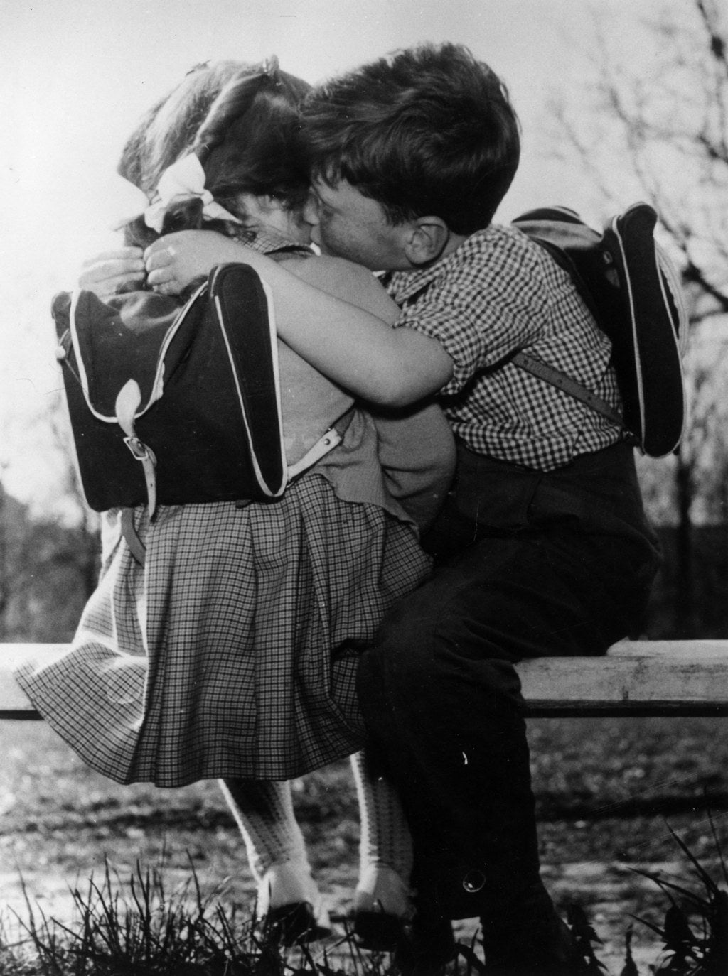 A couple of young children share an affectionate peck on the cheek. 1981.