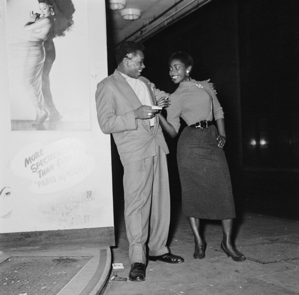 A young couple pose outside the 'Club Americana', a Saturday night jazz club open from midnight until 7 a.m., London. November 1955.
