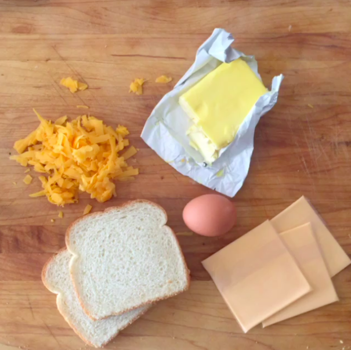Two slices of bread, an egg, butter, and lots of cheese. We used shredded cheddar and sliced American cheese, but feel free to go wild.
