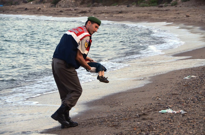 A paramilitary police officer carries a lifeless migrant boy who is believed to be among a number of others killed after boats carrying them to the Greek island of Kos capsized.