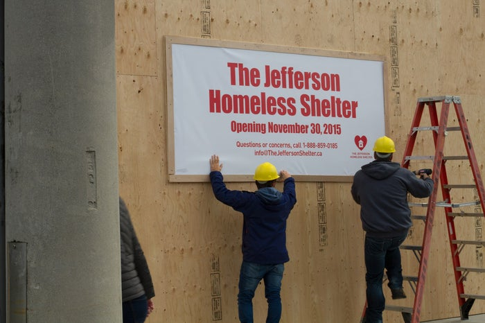 Workers put up the sign on a boarded-up storefront in early October.