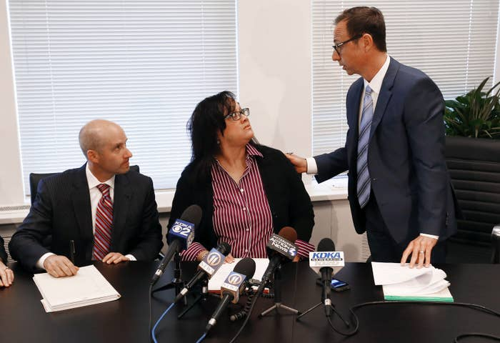 Renita Hill, center, sits between two of her attorneys.