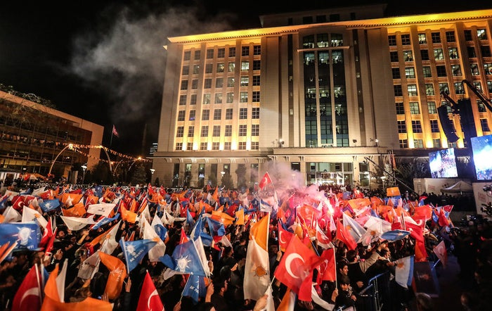 People wave flags outside the ruling AKP party headquarters in Ankara on Sunday.