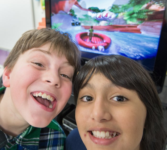 Sawyer Whitely and Michael Mendoza, who are autistic, pose for a photo while playing video games.