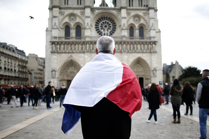 A man observes a minute of silence in front of the Notre Dame Cathedral in Paris, Nov. 16.
