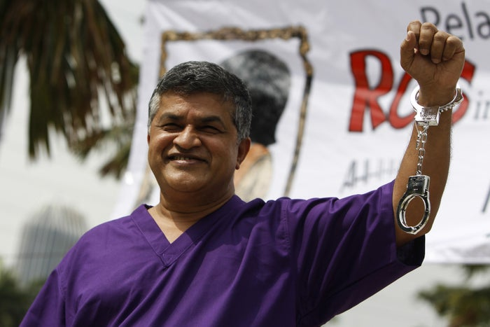 Zunar wearing a prison outfit and plastic handcuffs poses after being released on bail in February over government allegations he tweeted seditious remarks following a court ruling on Anwar Ibrahim's case.