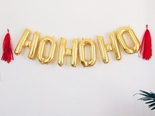"""Add a bit of fun to your decor with gold foil letter balloons. The best part is that you can make the banner say whatever you want, like your company's name or """"Happy Holidays."""""""