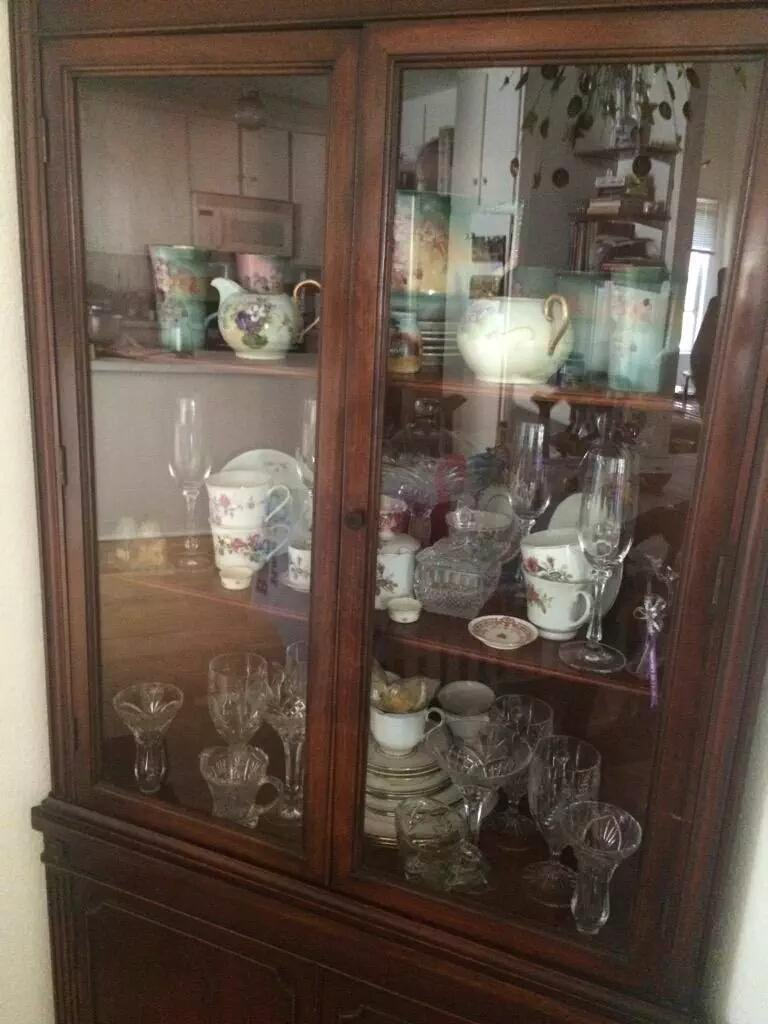 A glass-doored wooden china cabinet filled with china