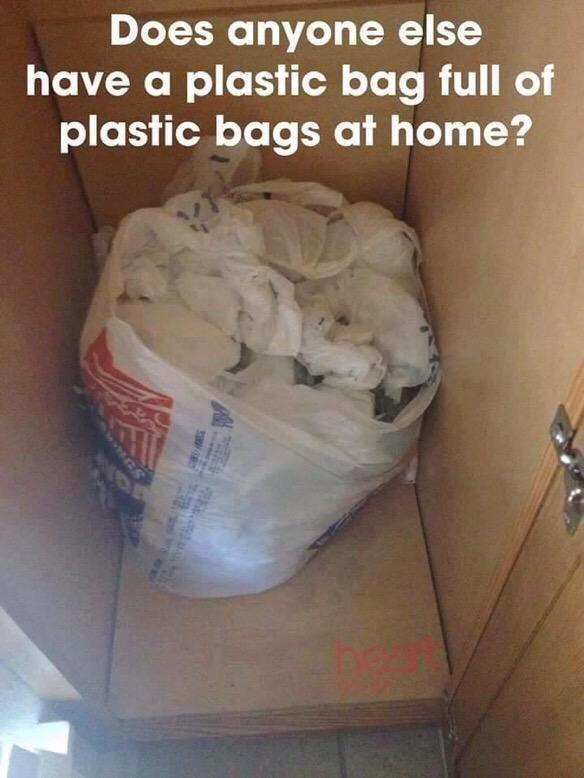 A cabinet open with a plastic bag inside filled with more plastic bags