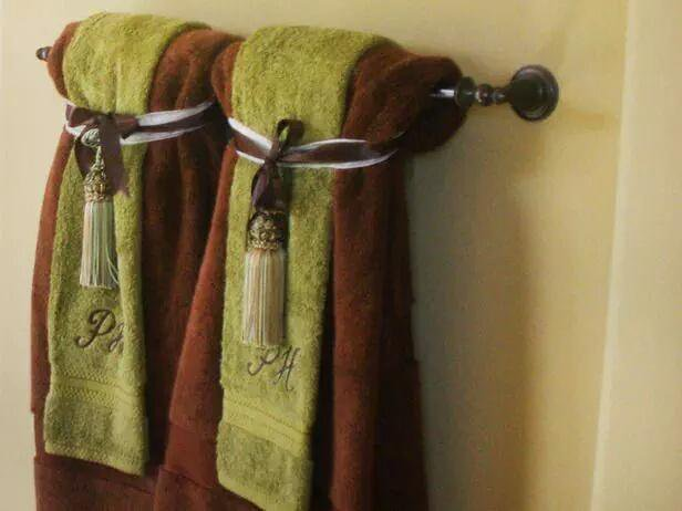 Fancy brown and green towels hanging on a towel bar